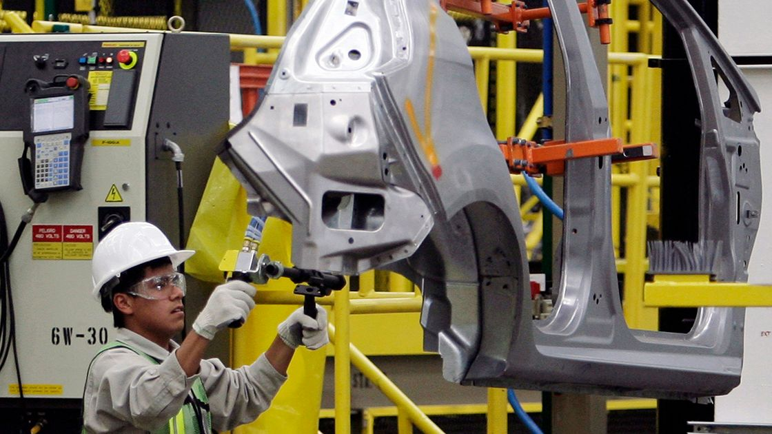 **  TO GO WITH MEXICO MAQUILAS  ** In this Oct. 6, 2009, file photo, an assembly line worker holds a part of a Ford Fiesta at Ford
