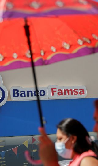 Women walk past a branch of Banco Ahorro Famsa, the savings bank arm of retailer Grupo Famsa, in Ciudad Juarez