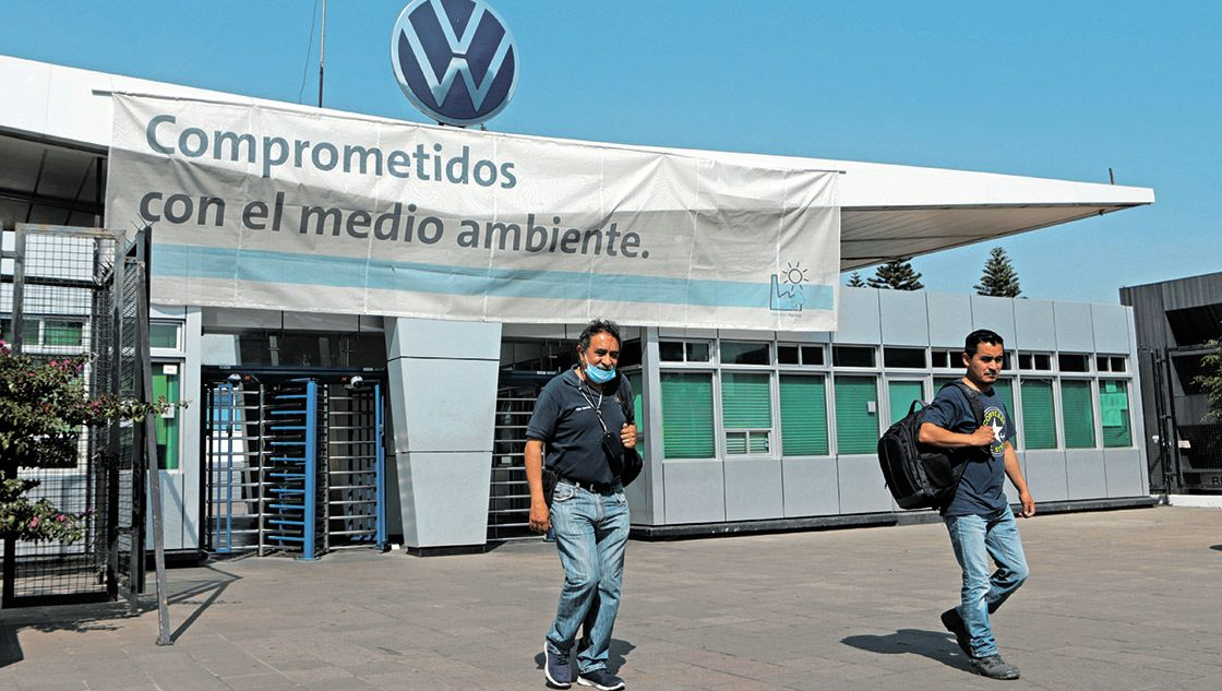FILE PHOTO: Employees leave the Volkswagen (VW) plant as the company will temporarily close its factories in Mexico amid growing worries over the spread of the coronavirus disease (COVID-19), in Puebla