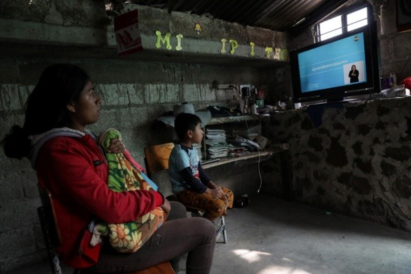 Oscar Hernandez, 5, follows a televised class at home next to his aunt Graciela Hernandez, as millions of students returned to classes virtually after schools were ordered into lockdown in March, due to the coronavirus disease (COVID-19) outbreak, in Chilcuautla, Hildalgo state, Mexico August 24, 2020. REUTERS/Henry Romero